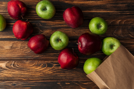 top view of ripe red and green apples with paper bag on wooden table Imagens