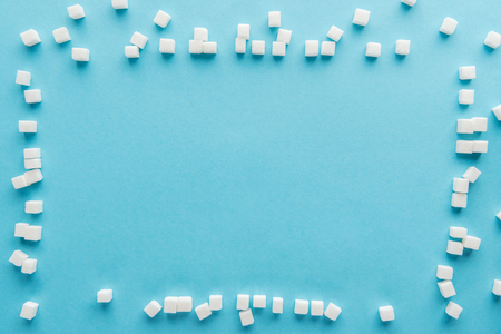 top view of frame made of sugar cubes with copy space on blue background Stock Photo