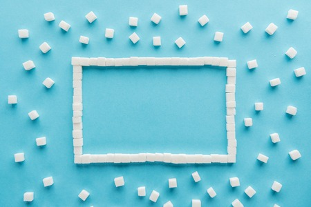 flat lay of frame made of sugar cubes with copy space on blue background