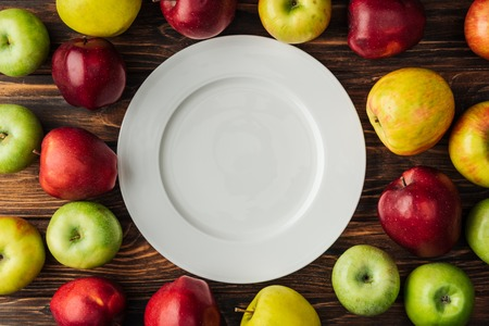 top view of white plate and ripe multicolored apples on wooden table