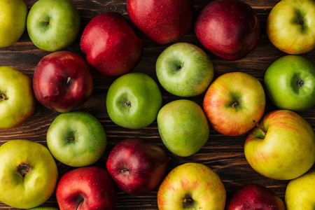 top view of ripe multicolored apples on wooden table Banco de Imagens