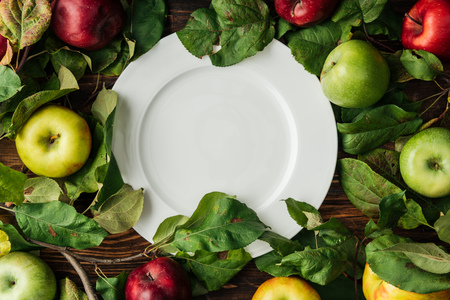 top view of white plate, multicolored apples and  branches with leaves on wooden table