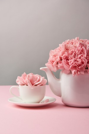close-up view of beautiful pink carnation flowers in white teapot and cup on grey