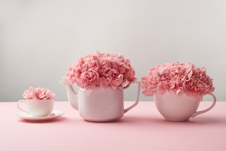 beautiful tender pink flowers in white teapot and cups on grey
