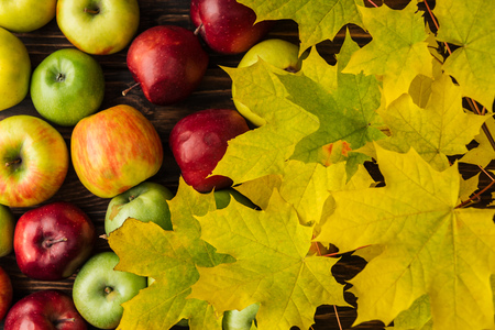 top view of ripe multicolored apples and yellow maple leaves on wooden table