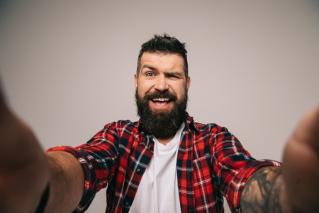 cheerful bearded man winking and taking selfie, isolated on grey