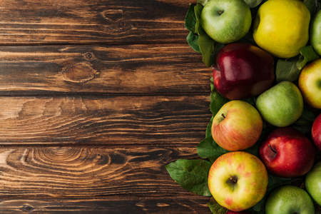 top view of ripe multicolored apples and leaves on wooden table