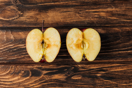 top view of cut ripe apple halves on wooden table