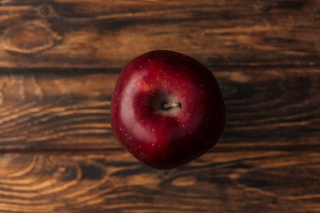 top view of ripe red delicious apple on wooden table