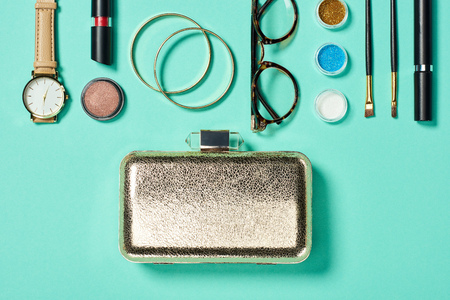 Top view of watch, lipstick, bracelets, glasses, eyeshadow, blush, clutch, cosmetic brushes and mascara