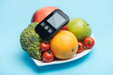glucometer on plate with vegetables and fruits on blue background