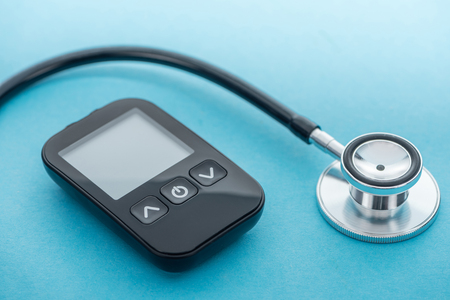 close up view of glucometer and stethoscope on blue background