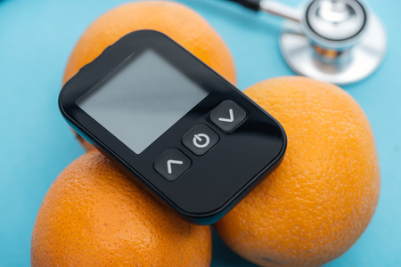 close up view of glucometer on oranges with stethoscope on blue background Zdjęcie Seryjne