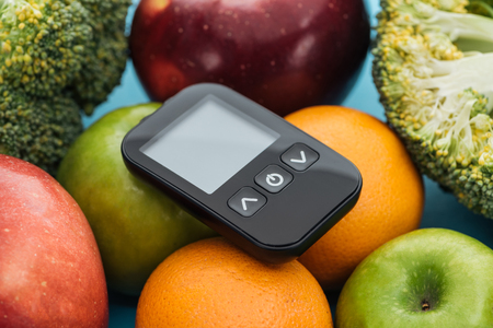 close up view of glucometer among fruits and broccoli on blue background