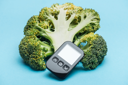 black glucometer with three broccoli on blue background