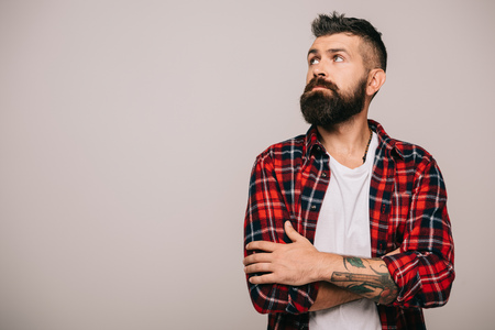 thoughtful bearded man in checkered shirt isolated on grey Imagens