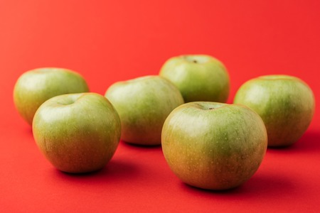 large ripe green apples on red background
