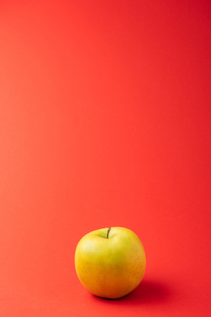 large golden delicious apple on red background