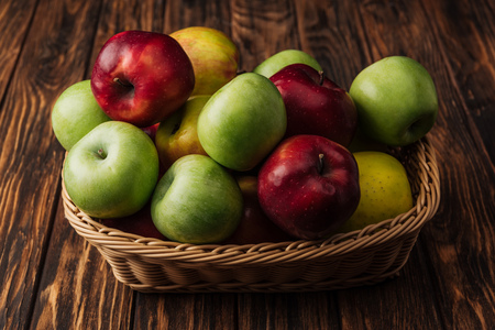 wicker basket with delicious red, green and yellow apples on wooden table Stock Photo