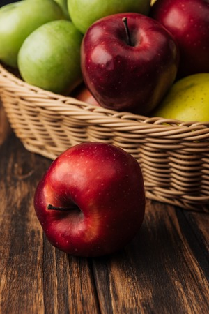 red delicious apple with fruit wicker basket at background Stock Photo