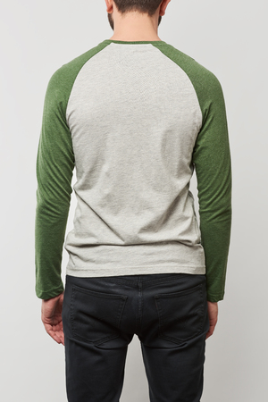 partial view of man in raglan sleeve baseball shirt with copy space isolated on grey