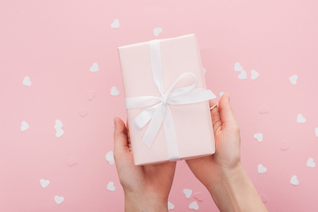 cropped view of woman holding gift box and paper hearts isolated on pink