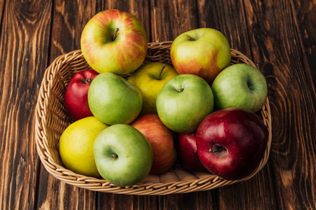 wicker basket with ripe multicolored apples on rustic wooden table