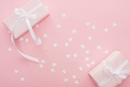 top view of gift boxes with ribbons and paper hearts isolated on pink Stock Photo