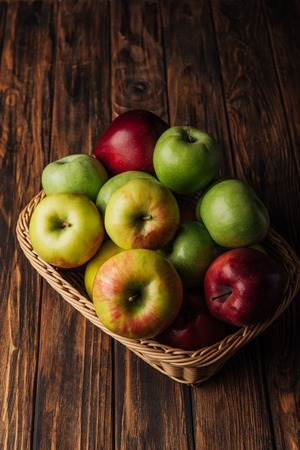 red, green and golden apples in wicker basket on rustic wooden table Stock Photo