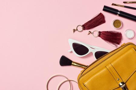 Bovenaanzicht van armbanden, oorbellen, zonnebrillen, mascara, cosmetische penselen, oogschaduw en tas op roze achtergrond Stockfoto