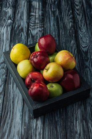 wooden box with ripe red, green and golden apples on table