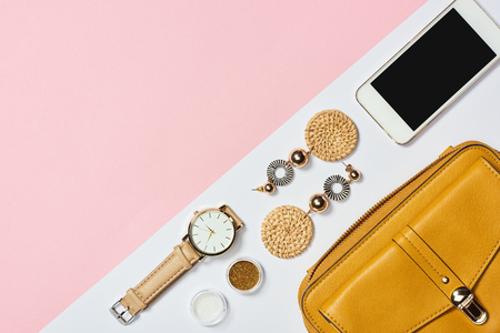 Top view of earrings, eyeshadow, watch, smartphone and yellow bag