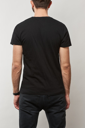back view of man in black t-shirt with copy space isolated on grey