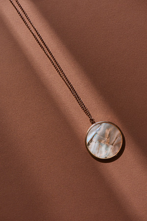 top view of beautiful round locket with marble on brown surface with sunlight Reklamní fotografie