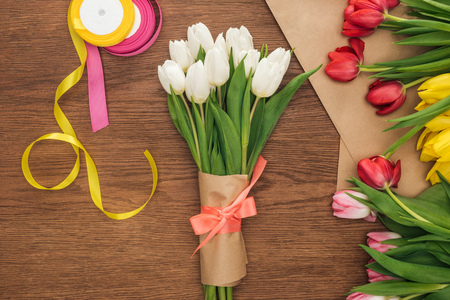 top view of spring bouquet, tulips, ribbons and craft paper on wooden background