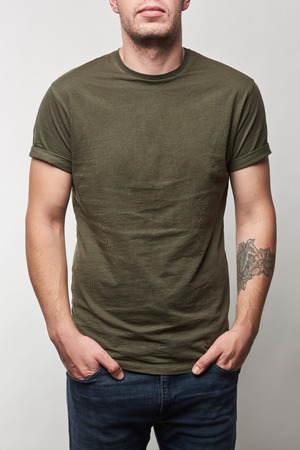 partial view of tattooed man in khaki t-shirt with copy space isolated on grey Reklamní fotografie