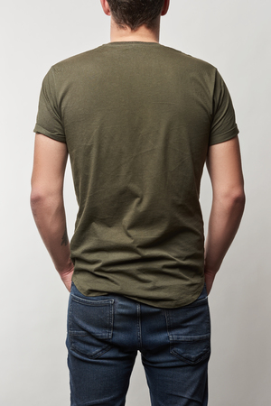 back view of man in khaki t-shirt with copy space isolated on grey Stok Fotoğraf