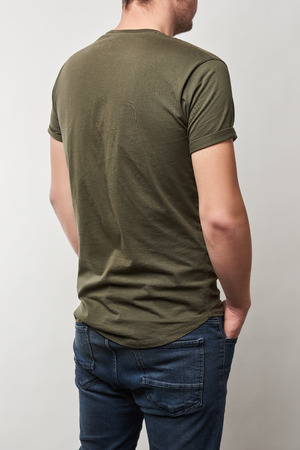 back view of man in khaki t-shirt with copy space isolated on grey 스톡 콘텐츠