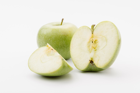 cut and whole delicious green apples on white background