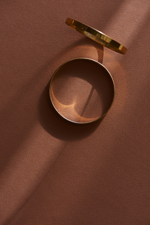 top view of two beautiful golden rings on brown surface with sunlight