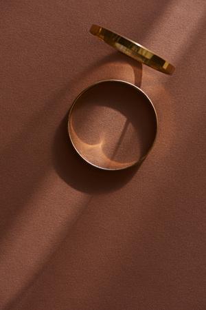 Vista superior de dos hermosos anillos dorados sobre superficie marrón con luz solar