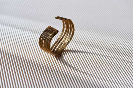 beautiful golden ring on striped white surface with sunlight
