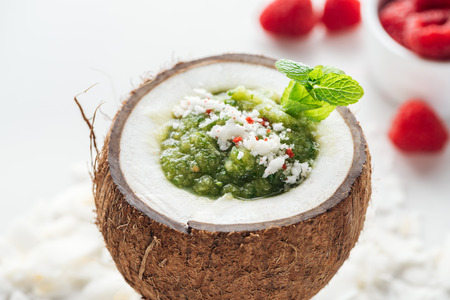 fresh green smoothie in coconut decorated with mint