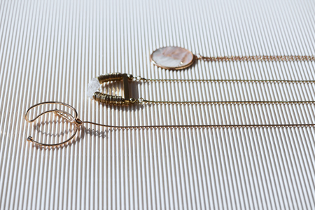 beautiful luxury necklaces and round locket with marble on striped white surface with sunlight Reklamní fotografie