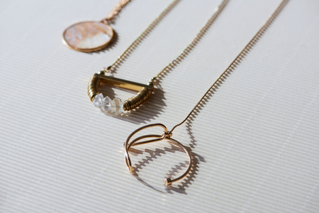close up of beautiful luxury necklaces and round locket with marble on striped white surface with sunlight Reklamní fotografie - 116497864