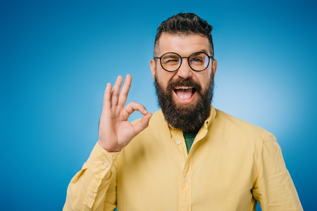 happy bearded man in eyeglasses winking and showing ok sign, isolated on blue