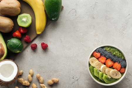 top view of smoothie bowl with fresh fruits and nuts on grey background Stock Photo