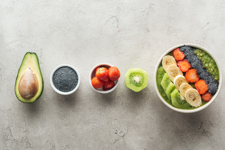 top view of healthy smoothie bowl with fresh fruits and ingredients on grey background
