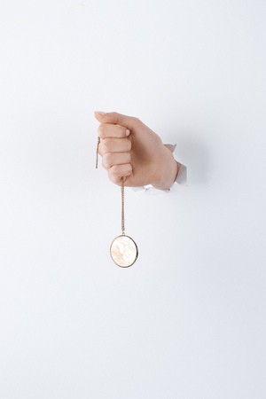 cropped image of woman holding hand with stylish round locket with marble through white paper Reklamní fotografie - 116498419