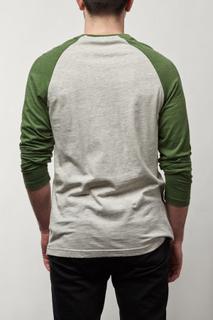 back view of man in raglan sleeve baseball shirt with copy space isolated on grey Stock Photo